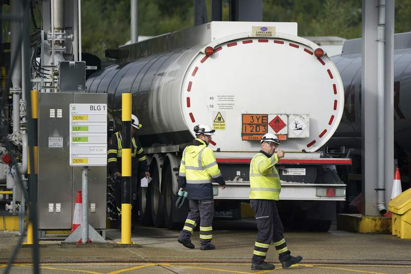 Workers at Buncefield oil depot, known as the Hertfordshire Oil Storage Terminal, in Hemel Hempstead, England, Monday, Oct. 4, 2021. British military personnel have begun delivering fuel to gas stations after a shortage of truck drivers disrupted supplies for more than a week, leading to long lines at the pumps as anxious drivers scrambled to fill their tanks. About 200 servicemen and women were deployed Monday to boost deliveries after undergoing training at commercial fuel depots last week, the government said. (Joe Giddens/PA via AP)