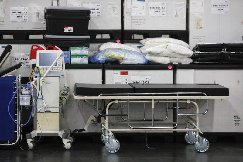 FILE - This Monday, March 23, 2020, file photo shows medical supplies and a stretcher displayed before a news conference at the Jacob Javits Center in New York. Health care workers are dreading the prospect of deciding which patients would get a ventilator that could save their lives. (AP Photo/John Minchillo, Fle)