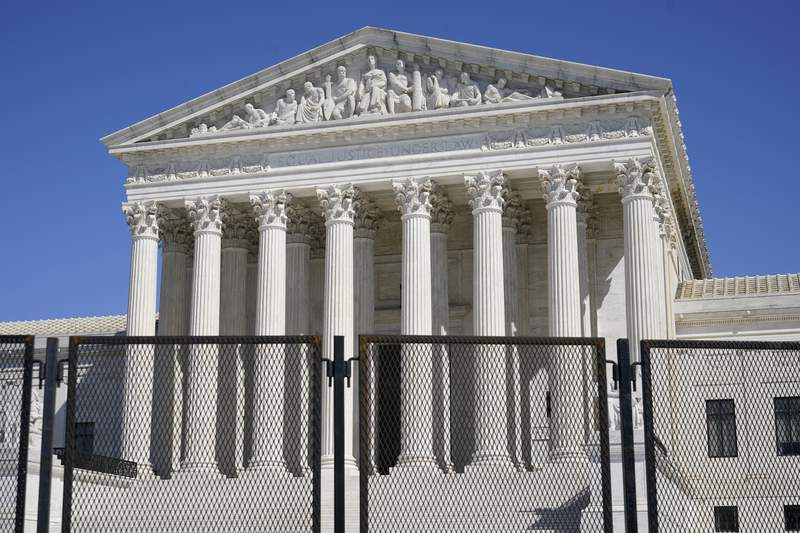 FILE - In this March 21, 2021, file photo security fencing surrounds the Supreme Court building on Capitol Hill in Washington. Biden on Friday, April 9, ordered a study of adding seats to the Supreme Court, creating a bipartisan commission that will spend the next 180 days examining the incendiary political issues of expanding the court and instituting term limits for justices on the highest bench. (AP Photo/Patrick Semansky, File)
