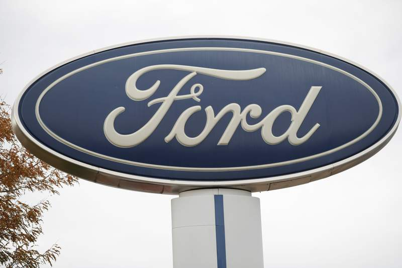 FILE - In this Oct. 20, 2019, file photo, the company logo stands over a long row of unsold vehicles at a Ford dealership in Littleton, Colo. Ford is recalling about 2.5 million vehicles in the U.S., Canada and elsewhere because of a nagging door latch problem and a brake fluid leak. The door latch recall covers more than 2.1 million cars, SUVs and vans in the U.S. The latches can fail and cause the doors to open while the vehicles are moving. It's the third recall for the same problem. (AP Photo/David Zalubowski, File)