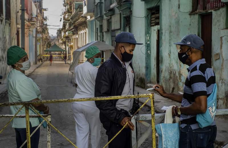 Un residente muestra su identificacin a un oficial de polica que est limitando el acceso a un vecindario como una forma de frenar la propagacin de la pandemia de COVID-19, mientras enfermeras estn detrs en La Habana, Cuba, el lunes 22 de febrero de 2021. (AP Foto/Ramon Espinosa)
