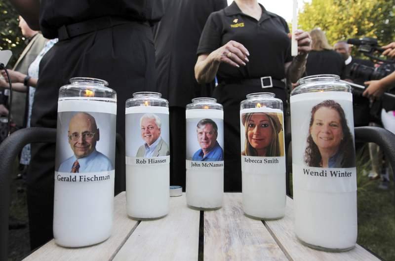 Fotografa de archivo del 29 de junio de 2018 de veladoras con fotos de cinco empleados del peridico Capital Gazette durante una vigilia frente a la redaccin en donde fueron asesinados en Annapolis, Maryland. (AP Foto/Jose Luis Magana, Archivo)