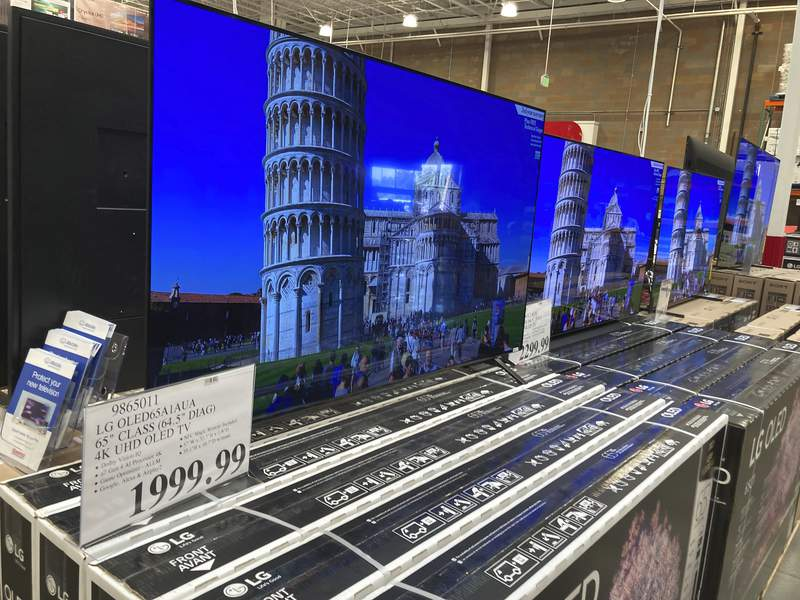 A sign displays the price of a 65-inch television lined up with countless other televisions in a Costco warehouse on Thursday, June 17, 2021, in Loen Tree, Colo.    The Commerce Department said Thursday, June 24 that growth in the gross domestic product, the countrys total output of goods and services, was unchanged from two previous estimates.(AP Photo/David Zalubowski)