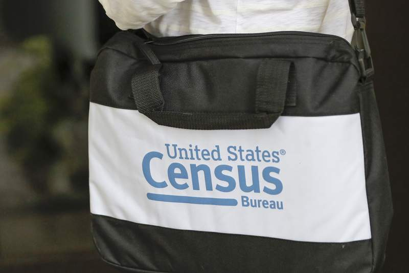 A briefcase of a census taker is seen as she knocks on the door of a residence Tuesday, Aug. 11, 2020, in Winter Park, Fla. A half-million census takers head out en mass this week to knock on the doors of households that haven't yet responded to the 2020 census. (AP Photo/John Raoux)
