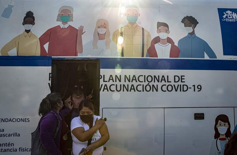 Mujeres salen de un autobs que se usa para inyectar la vacuna contra COVID-19 en Santiago, Chile, el mircoles 26 de mayo de 2021. (AP Foto/Esteban Felix)