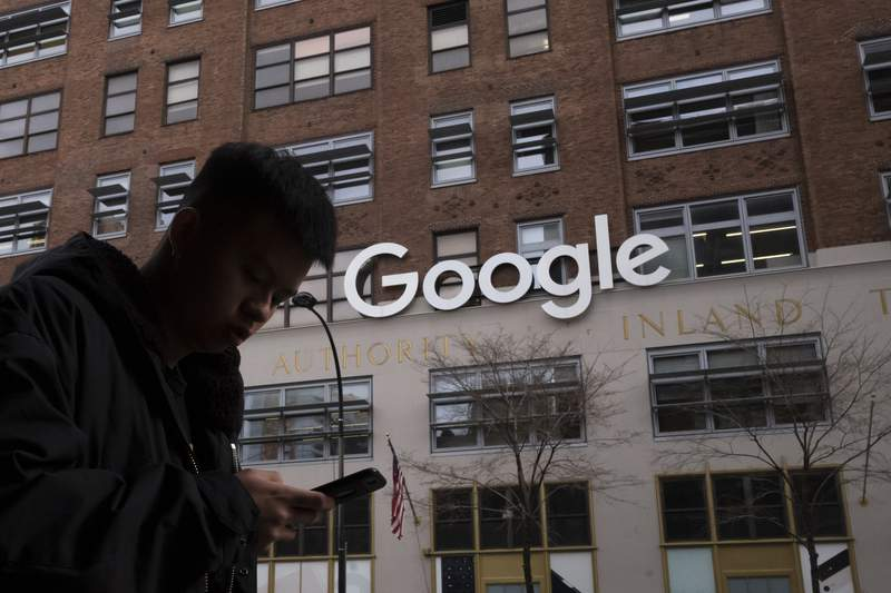 FILE - In this file photo dated Monday, Dec. 17, 2018, a man using a mobile phone walks past Google offices in New York. Google is appealing a 500 million euro ($591 million) fine, Wednesday, Sept. 1, 2021, issued by French regulators over its handling of negotiations with publishers in a dispute over copyright.   (AP Photo/Mark Lennihan, File)