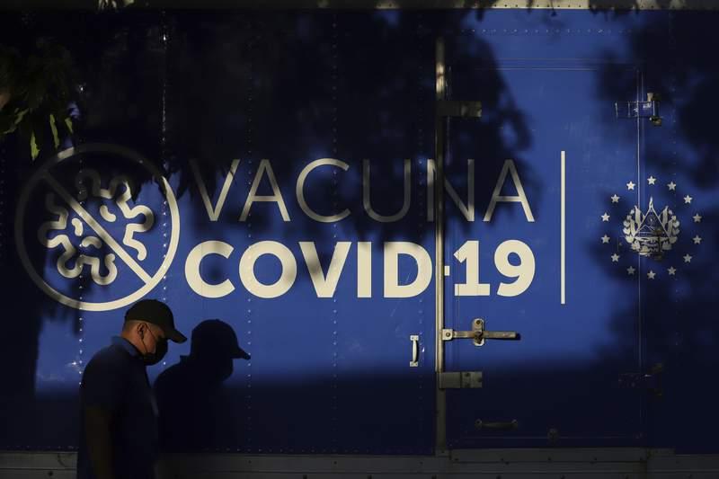 Un conductor pasa junto a un camin refrigerado del Ministerio de Salud que transporta dosis de vacunas para el COVID-19 que el gobierno de El Salvador don a Honduras antes de partir de San Salvador, El Salvador, el jueves 13 de mayo de 2021. (AP Foto/Salvador Melndez)