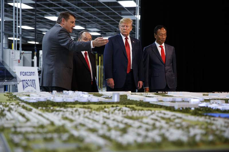 FILE - In this June 28, 2018 photo, President Donald Trump takes a tour of Foxconn with Foxconn chairman Terry Gou, right, and CEO of SoftBank Masayoshi Son in Mt. Pleasant, Wis.  Foxconn Technology Group will qualify for up to $80 million in state tax incentives under a new contract agreed to on Tuesday, April 20, 2021 that downsizes the scale of credits as the size of the envisioned manufacturing facility has also shrunk. Gov. Tony Evers announced details of the new contract.  (AP Photo/Evan Vucci, File)
