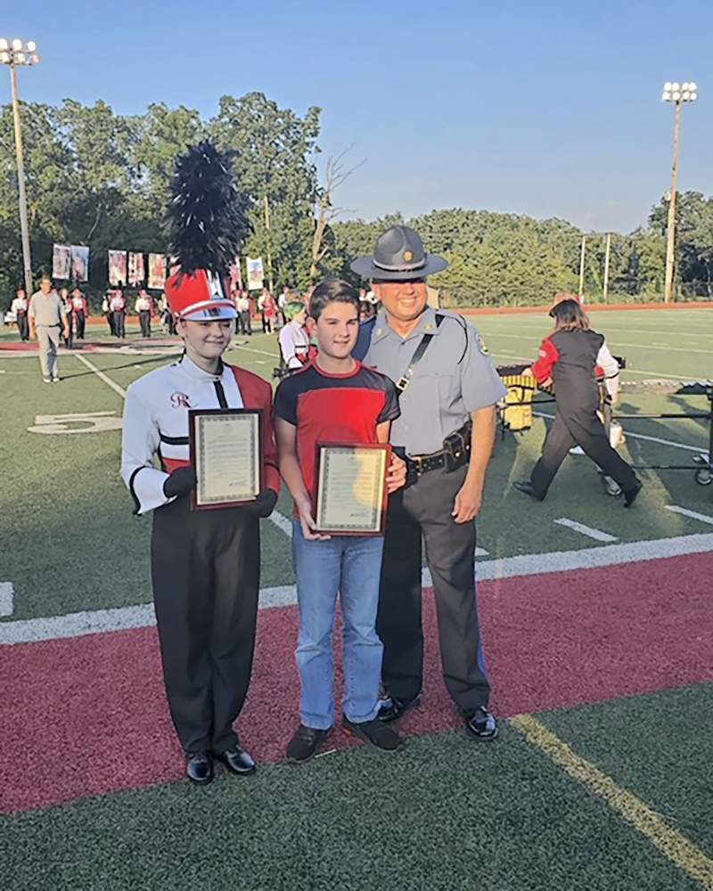 In this photo made Friday, Aug. 27, 2021, and provided by the provided by Chris James of the St. James Press, high school sophomore Emilee Williams, left, and seventh-grader Tandon Baker are honored before a football game by Missouri State Highway Patrol Col. Eric Olson for their heroic actions after a school bus driver lost consciousness. The driver passed out while driving on Aug. 25, 2021, and Brandon rushed to the front of the bus and applied the brake. Emilee called 911 and comforted the young children on the bus. (Chris James/ St. James Press via AP)