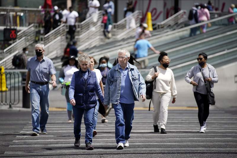 Masked and unmasked pedestrians walk across Las Vegas Boulevard, Tuesday, April 27, 2021, in Las Vegas. The Centers for Disease Control and Prevention eased its guidelines Tuesday on the wearing of masks outdoors, saying fully vaccinated Americans don't need to cover their faces anymore unless they are in a big crowd of strangers. (AP Photo/John Locher)