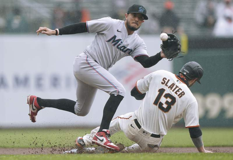 Austin Slater of the San Francisco Giants steals second base sliding in ahead of the throw to Miguel Rojas of the Miami Marlins in the first inning at Oracle Park on April 25, 2021 in San Francisco, California.