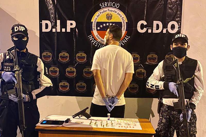 In this March 31, 2020, photo, Venezuelan police officers present a suspect arrested at a multiday party in Caracas, Venezuela, that violated Nicolas Maduros order on large gatherings during the coronavirus pandemic. (Courtesy of Venezuelan Chief Prosecutors Office via AP)