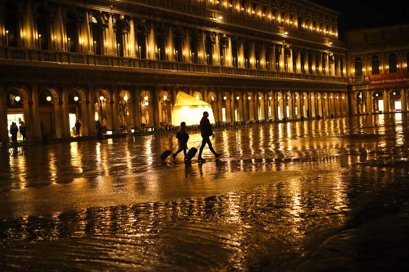 FILE - In this March 2, 2020, file photo, tourists pull their trolleys as they walk through a nearly empty St. Mark's Square on a rainy day in Venice. America's failure so far to contain the spread of the coronavirus as it moves across the country has been met with astonishment and alarm on both sides of the Atlantic. (AP Photo/Francisco Seco, File)