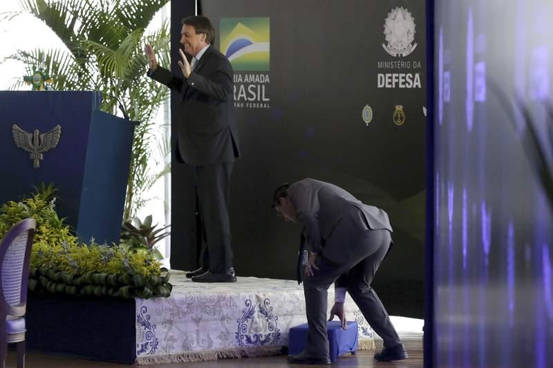 El presidente brasileo Jair Bolsonaro sonre tras tropezar al subir a un podio para dirigirse a generales de las fuerzas armadas el mircoles 9 de diciembre de 2020 en el club de Aeronutica, en Brasilia. (AP Foto/Eraldo Peres)