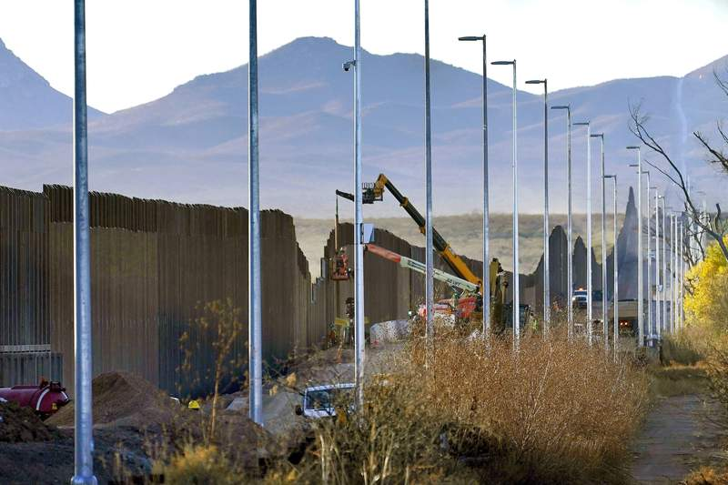 FILE - In this Dec. 8, 2020, file photo, crews construct a section of border wall in San Bernardino National Wildlife Refuge in Douglas, Ariz. A small town in Arizona has declared a state of emergency over migrant families being dropped there as a growing number of border communities grapple with how to get the families to shelters in bigger cities that can help them. Gila Bend Mayor Chris Riggs made the declaration Tuesday, March 23, 2021, saying the town does not have the resources or funds to support migrants, many who arrive with hopes of seeking asylum and making their home in America. (AP Photo/Matt York, File)