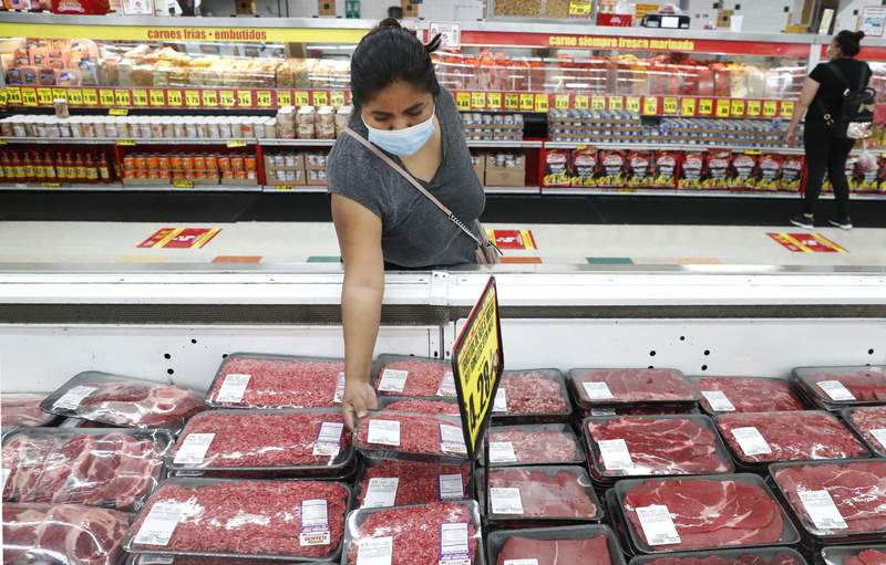 FILE - In this April 29, 2020 file photo, a shopper wears a mask as she looks over meat products at a grocery store in Dallas.   Wholesale prices rose a higher-than-expected 0.6% in April, driven by a sharp rise in food costs.   The increase, reported Thursday, May 13, 2021,  by the Labor Department, followed a sizable 1% advance in March.(AP Photo/LM Otero, File)