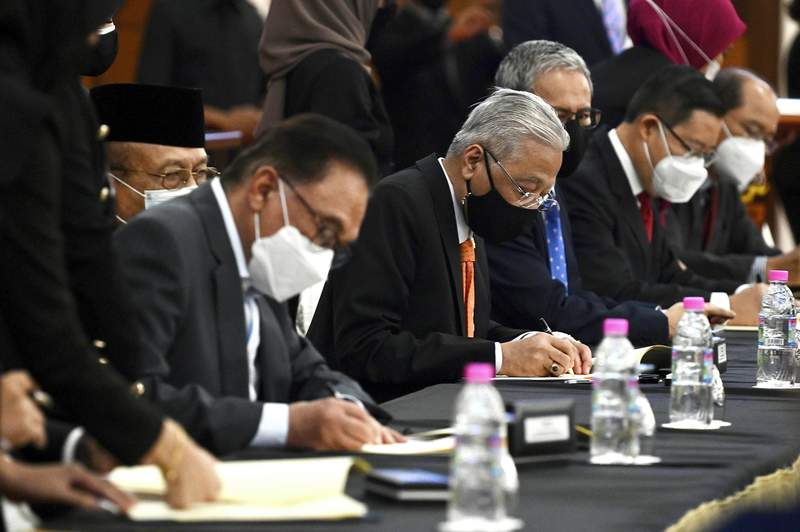 In this photo released by Malaysia's Department of Information, Malaysian Prime Minister Ismail Sabri Yaakob, center, and opposition leader Anwar Ibrahim, left, sign documents during a ceremony at Parliament at the parliament house in Kuala Lumpur, Malaysia, Monday, Sept. 13, 2021. Ismail signed an unprecedented cooperation pact with the main opposition bloc led by Anwar. The deal will prevent any bid to undermine Ismail's rule ahead of general elections due in two years. (Zarith Zulkifli/Malaysia's Department of Information via AP)