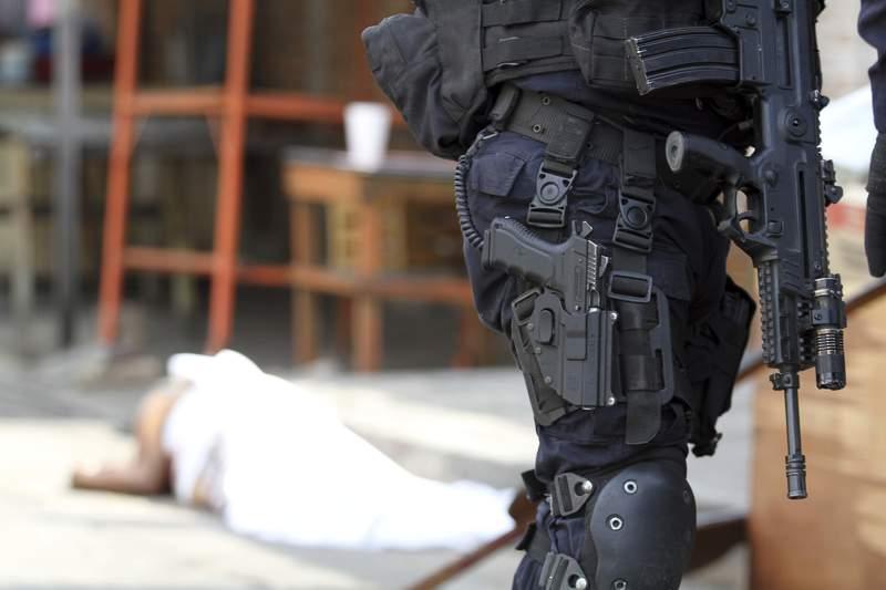 ARCHIVO - En esta fotografa del 2 de enero de 2019, un agente de la polica vigila la escena de un homicidio despus de que un hombre falleci tras ser baleado en Acapulco, Mxico. (AP Foto/Bernardino Hernndez, archivo)