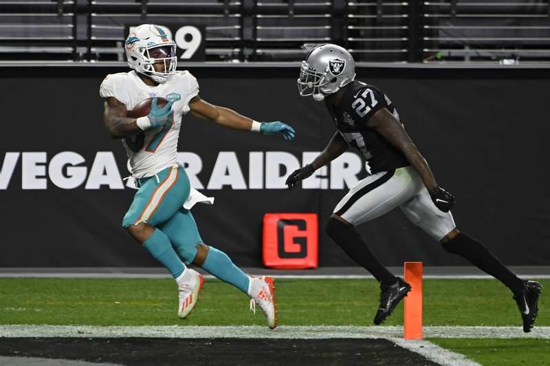Miami Dolphins running back Myles Gaskin (37) scores a touchdown against Las Vegas Raiders cornerback Trayvon Mullen (27) during the second half of an NFL football game, Saturday, Dec. 26, 2020, in Las Vegas. (AP Photo/David Becker)