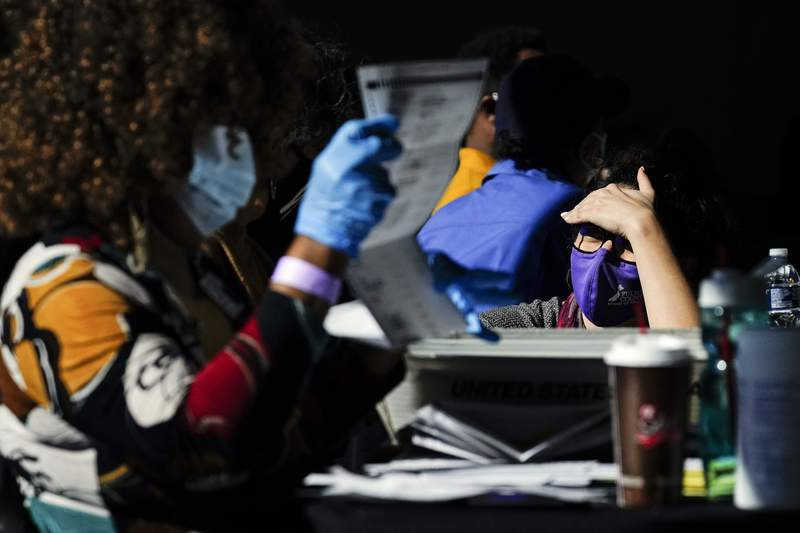 An election supervisor answer questions from an election worker as vote counting in the general election continues at State Farm Arena on Thursday, Nov. 5, 2020, in Atlanta. (AP Photo/Brynn Anderson)