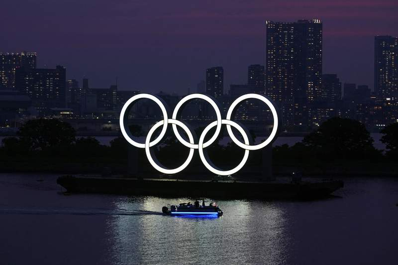 FILE - In this June 3, 2020, photo, the Olympic rings float in the water at sunset in the Odaiba section in Tokyo. The Japanese public is being prepared for the reality of next year's postponed Olympics where athletes are likely to face quarantines, spectators will be fewer, and the delay will cost taxpayers billions of dollars. In the last several weeks, IOC President Thomas Bach has given selected interviews outside Japan and hinted at empty stadiums, quarantines and virus testing. (AP Photo/Eugene Hoshiko, File)
