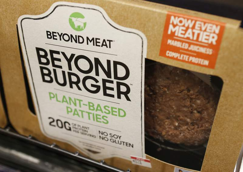 FILE - In this June 27, 2019, file photo, a meatless burger patty called Beyond Burger by Beyond Meat is displayed at a grocery store in Richmond, Va. Plant-based food company Beyond Meat will be partnering with several major fast food chains in the coming years to expand offerings that could eventually include plant-based burgers, chalupas or toppings on a stuffed-crust pizza. They announced on Thursday, Feb. 25, 2021, distribution agreements with McDonald's as well as with Yum Brands, the parent company of KFC, Taco Bell and Pizza Hut. (AP Photo/Steve Helber, File)