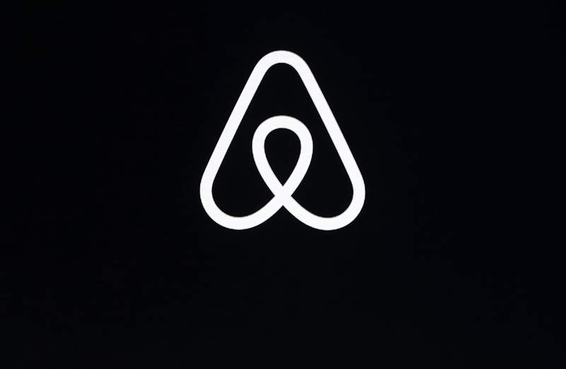 FILE - This Feb. 22, 2018, file photo shows an Airbnb logo during an event in San Francisco. Home-sharing site Airbnb posted a $3.9 billion loss in the fourth quarter of 2020 as it suffered from the pandemic downturn in travel and recorded one-time costs for becoming a public company. (AP Photo/Eric Risberg, File)