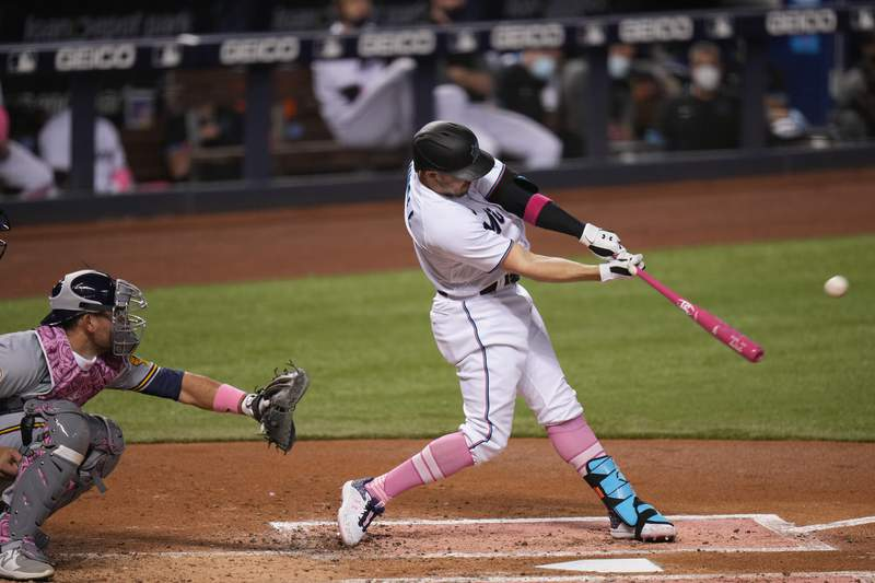 Adam Duvall of the Miami Marlins bats in the second inning against the Milwaukee Brewers at loanDepot park on May 09, 2021 in Miami, Florida. Players from both teams are wearing pink in their uniforms to celebrate Mother's Day.