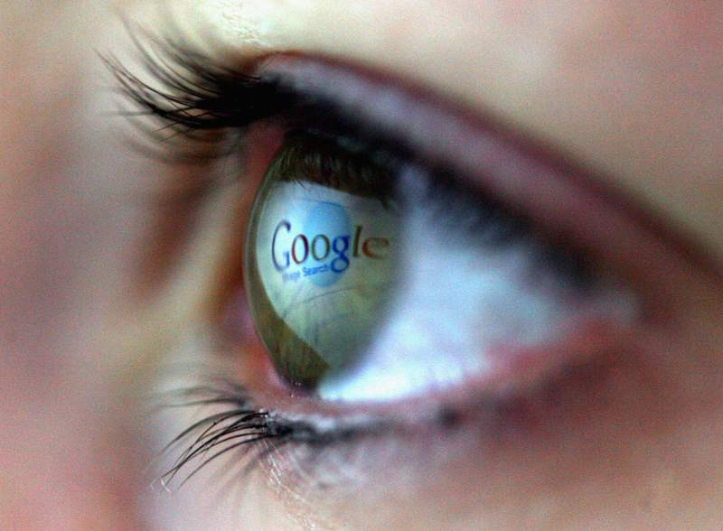 The Google logo is reflected in the eye of a girl.