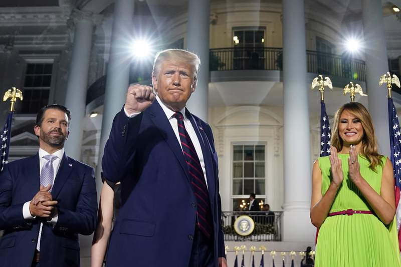 From left, Donald Trump Jr., President Donald Trump and first lady Melania Trump stand on the South Lawn of the White House on the fourth day of the Republican National Convention, Thursday, Aug. 27, 2020, in Washington. (AP Photo/Evan Vucci)