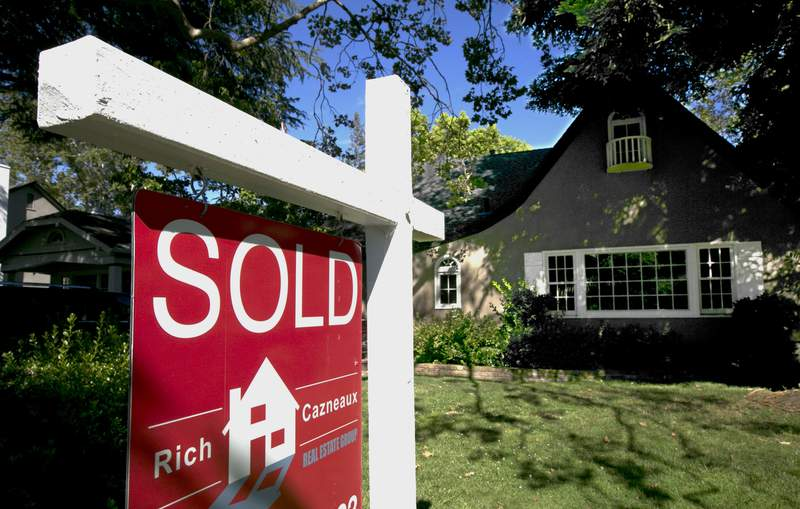 FILE - In this Wednesday, July 5, 2017, file photo, a sold sign is displayed in front of a house in Sacramento, Calif.  U.S. long-term mortgage rates hovered near all-time lows for the third straight week amid fresh signs of severe damage to the economy and the housing market from the shutdown spurred by the coronavirus pandemic. Mortgage buyer Freddie Mac says on Thursday, April 16, 2020,  the average rate on the benchmark 30-year home loan slipped to 3.31% this week from 3.33% last week.  (AP Photo/Rich Pedroncelli, File)