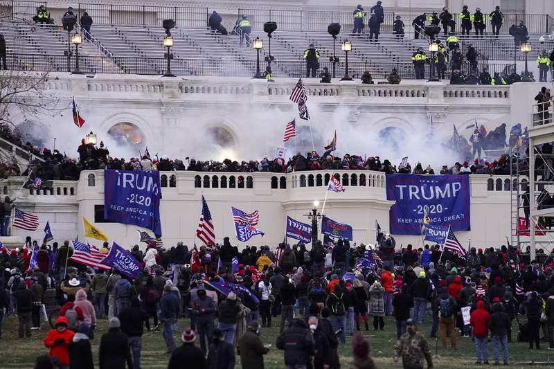 FILE - In this Wednesday, Jan. 6, 2021, file photo, violent protesters, loyal to President Donald Trump, storm the Capitol, in Washington. A pro-China network of fake and imposter accounts found a global audience on YouTube, Facebook and Twitter to mock the U.S. response to the COVID-19 pandemic as well as the deadly riot in Washington that left five dead, new research published Thursday, Feb. 4, 2021, found. (AP Photo/John Minchillo, File)