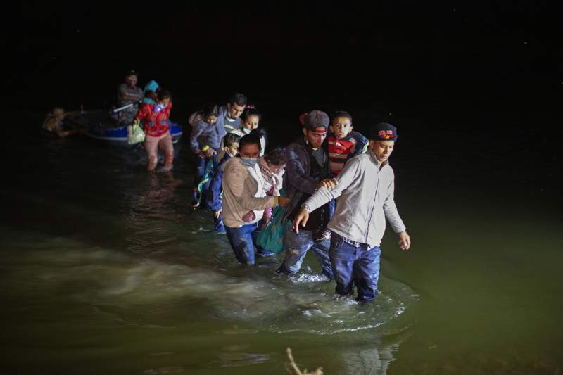 In this March 24, 2021 photo, migrant families, mostly from Central American countries, wade through shallow waters after being delivered by smugglers on small inflatable rafts on U.S. soil in Roma, Texas.  The Biden administration said Monday that four families that were separated at the Mexico border during Donald Trump's presidency will be reunited in the United States this week in what Homeland Security Secretary Alejandro Mayorkas calls just the beginning of a broader effort.   (AP Photo/Dario Lopez-Mills)
