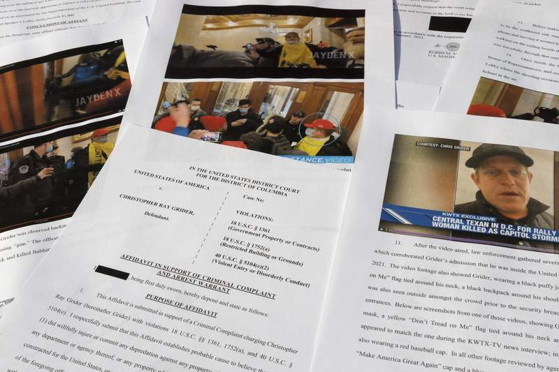 This May 20, 2021, photo shows the affidavit in support of the criminal complaint and arrest warrant for Christopher Ray Grinder. At least a dozen people charged in the Jan. 6 riot have cited crowd psychology to explain their out-of-character behavior or have claimed they became trapped in the flow of the crowd and were carried against their will into the Capitol. Grider said he came to Washington on Jan. 6 with no intention of rioting. But he got caught up in the mob of angry President Donald Trump supporters as it surged into the U.S. Capitol, breaking through police barriers and smashing through doors.  (AP Photo/Jon Elswick)