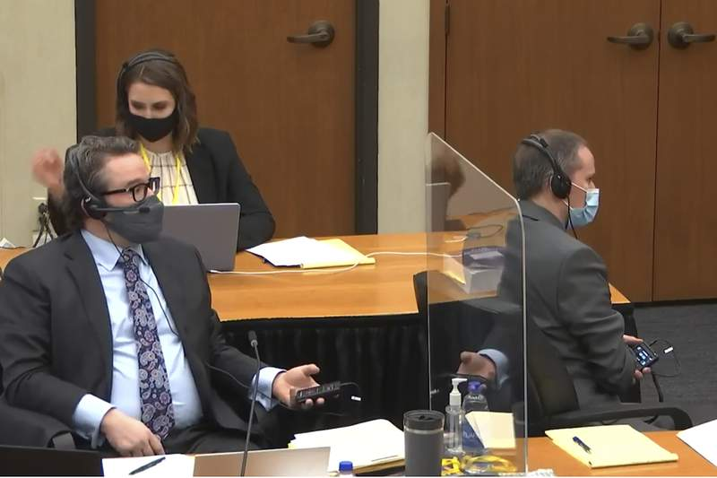 In this image from video, defense attorney Eric Nelson, left, Nelson's assistant Amy Voss, back, and former Minneapolis police officer Derek Chauvin, right, participate in a sidebar through headsets with Hennepin County Judge PeterCahill as he presides Monday, March 29, 2021, in the trial of Chauvin, in the May 25, 2020, death of George Floyd at the Hennepin County Courthouse in Minneapolis, Minn. (Court TV via AP, Pool)