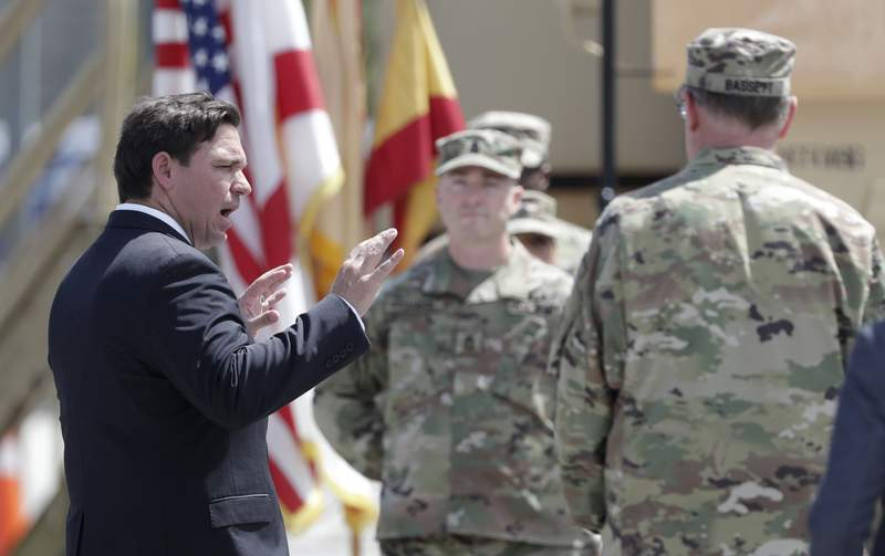 In this file photo, Gov. Ron DeSantis, left, talks with members of the Florida National Guard, Sunday, March 22, 2020, at Hard Rock Stadium in Miami Gardens, Fla.  (AP Photo/Wilfredo Lee)