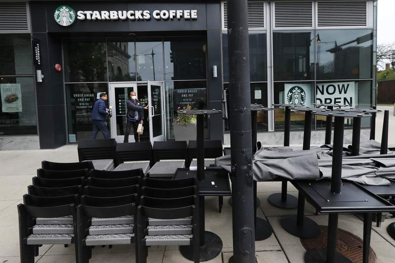 FILE - In this May 21, 2020 file photo, patrons to a Starbucks in the Chicago neighborhood of Hyde Park walk past stacked chairs and tables.  Starbucks says that the COVID-19 pandemic caused an approximately $3 billion to $3.2 billion decline in its third-quarter consolidated revenue. The coffee chain said Wednesday, June 10,  that the virus outbreak also lowered operating income by about $2 billion to $2.2. billion. (AP Photo/Charles Rex Arbogast)