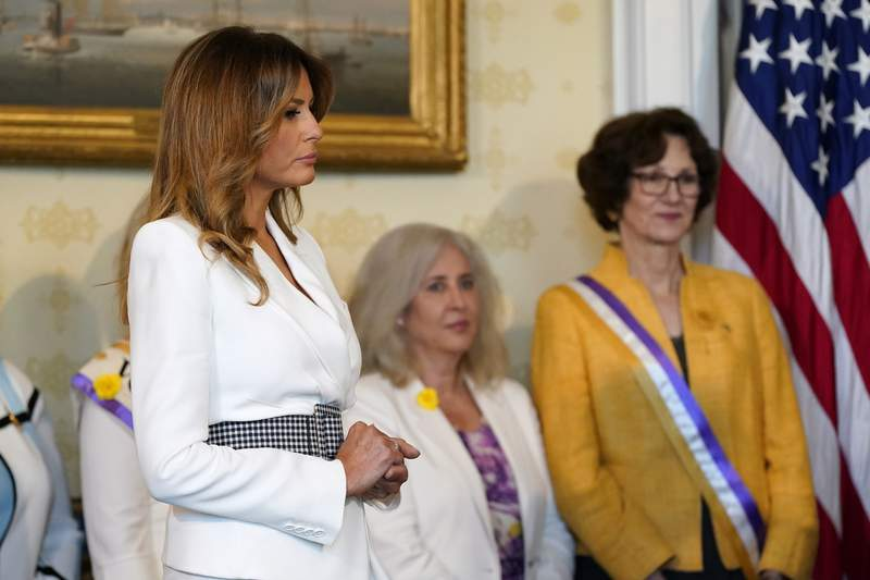 First lady Melania Trump listens as President Donald Trump speaks before signing a proclamation recognizing the 100th anniversary of the ratification of the 19th Amendment, Tuesday, Aug. 18, 2020, in the Blue Room of the White House in Washington. (AP Photo/Patrick Semansky)