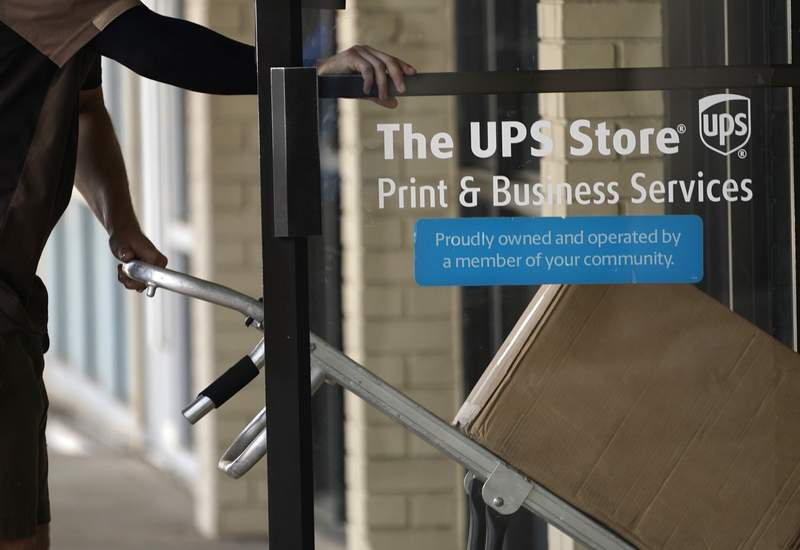 A UPS driver enters a United Parcel Service store with packages in Jackson, Miss., Monday, July 26, 2021. UPS second-quarter results topped Wall Streets view as the company continues to benefit from people increasingly having more and more products delivered to their homes.  (AP Photo/Rogelio V. Solis)