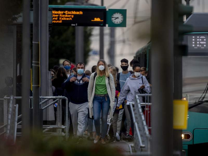 People wear face masks as they walk away from a subway station in Frankfurt, Germany, Thursday, Sept. 24, 2020. (AP Photo/Michael Probst)