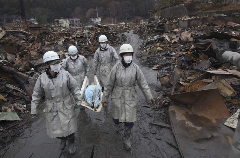On March 16, 2011, rescue workers carry a charred body from the rubble of a village destroyed by the devastating earthquake, fires and tsunami in Kesennuma, Miyagi province, Japan. The 9.0 magnitude strong earthquake struck offshore on March 11 at 2:46 p.m. local time, triggering a tsunami wave of up to 10 metres, which engulfed large parts of north-eastern Japan.
