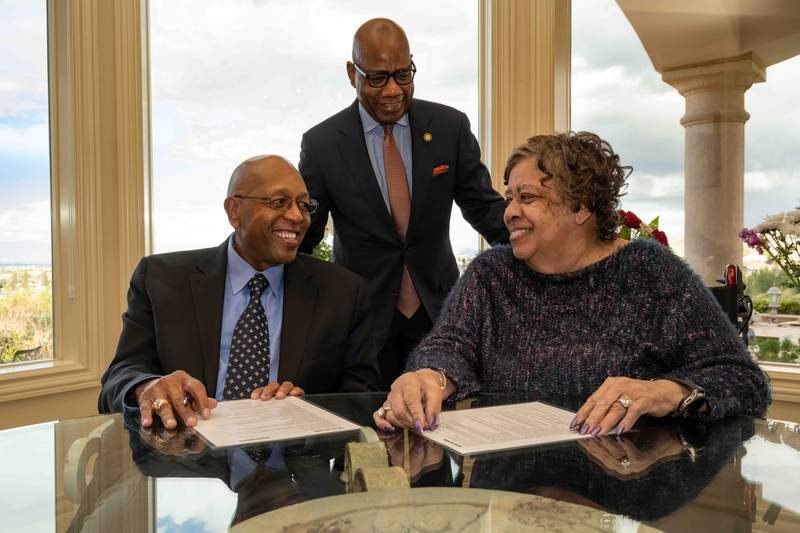 """In this photo provided by Morgan State University, Calvin Tyler Jr. and his wife, Tina, smile at each other after signing a giving pledge for $20 million to his alma mater, Morgan State University, as the university's president, David K. Wilson, looks on at the Tylers' home in Las Vegas on Saturday, Feb. 20, 2021. (Paul """"P.A."""" Greene/Morgan State University via AP)"""
