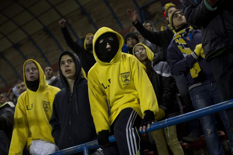 In this Tuesday, Jan. 29, 2013 photo Beitar Jerusalem F.C. soccer supporters watch a State Cup soccer match against Maccabi Umm al-Fahm F.C. in Jerusalem. Israel's Beitar Jerusalem soccer club, which has gained notoriety for never having an Arab player on its roster, announced on Monday, Dec. 7, 2020 that an Emirati investor has purchased a 50% stake in the team. The team said that Sheikh Hamad bin Khalifa Al Nahyan, a member of the United Arab Emirates royal family, has pledged to invest 300 million shekels, or about $90 million, into the club over the next decade. (AP Photo/Bernat Armangue)