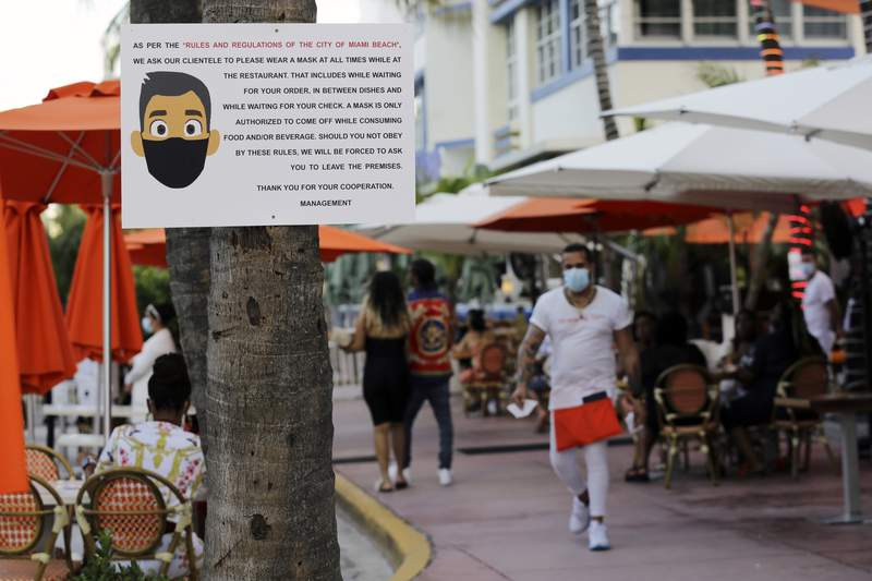 FILE - In this file photo, a sign informs customers at the Edison Hotel restaurant about wearing a protective face mask during the coronavirus pandemic along Ocean Drive in Miami Beach, Fla.  (AP Photo/Lynne Sladky, File)