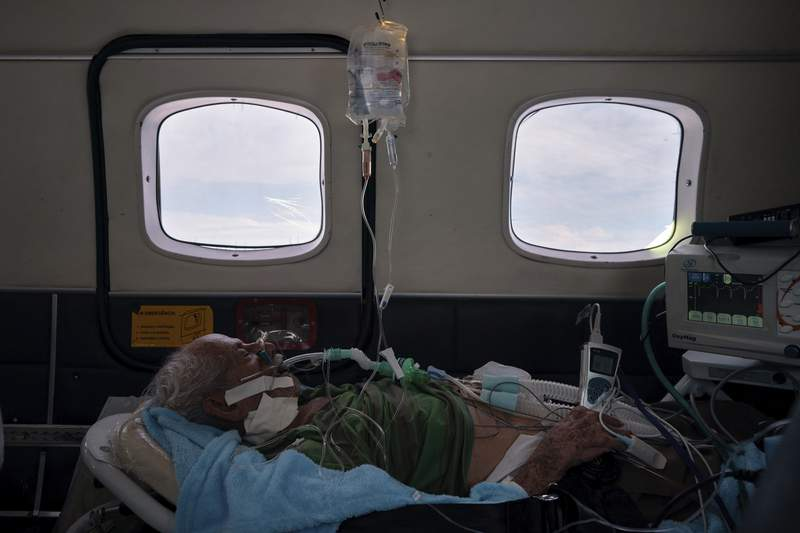 COVID-19 patient Sildomar Castelo Branco, 89, is treated onboard an aircraft as he is transferred from Santo Antnio do Ia to a hospital in Manaus in Brazil's Amazon state, Tuesday, May 19, 2020. (AP Photo/Felipe Dana)