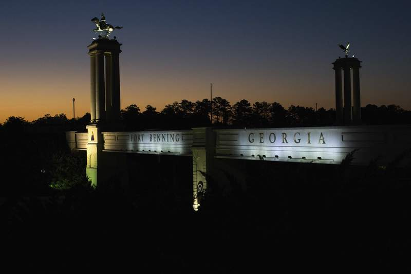 FILE - In this Oct. 16, 2015, file photo a bridge marks the entrance to the U.S. Army's Fort Benning as the sun rises in Columbus, Ga. An annual defense policy measure that has passed Congress every year since the Kennedy administration is in danger of cratering next month over a move by Democrats to rename military bases, such as Fort Benning, that are named after Confederate officers. (AP Photo/Branden Camp, File)