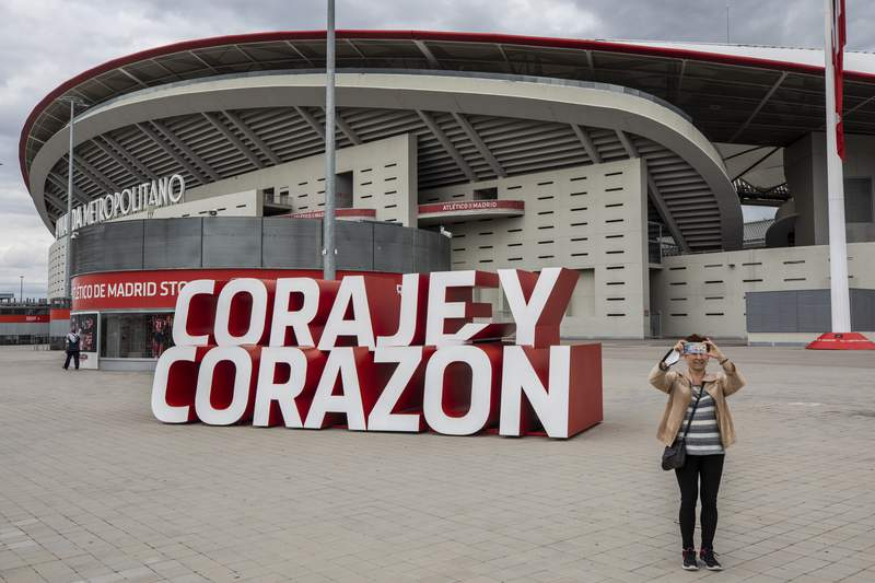 """A woman takes a snapshot in front Atletico Madrid's Wanda Metropolitano stadium in Madrid, Spain, Tuesday, April 20, 2021. A group of 12 elite English, Spanish and Italian clubs dramatically split European soccer on Sunday by announcing the formation of a largely-closed Super League. The Super League's founding chairman Florentino Perez on Tuesday, April 20, 2021 says the competition is being created to save soccer for everyone and not to make the rich clubs richer. The Real Madrid president says it's """"impossible"""" that players from the participating teams will be banned by UEFA. (AP Photo/Bernat Armangue)"""