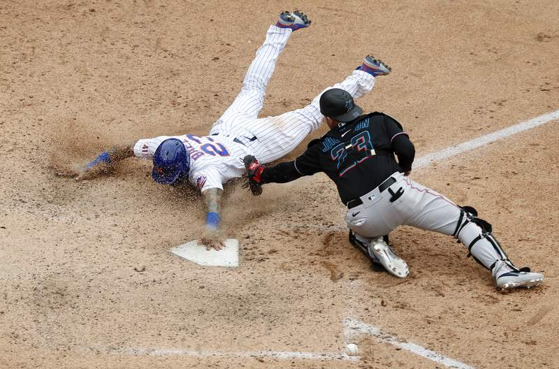 Javier Baez of the New York Mets slides home with the game winning run in the ninth inning against Alex Jackson of the Miami Marlins at Citi Field on August 31, 2021 in New York City.  This is a continuation of the April 11 game which was suspended due to inclement weather.