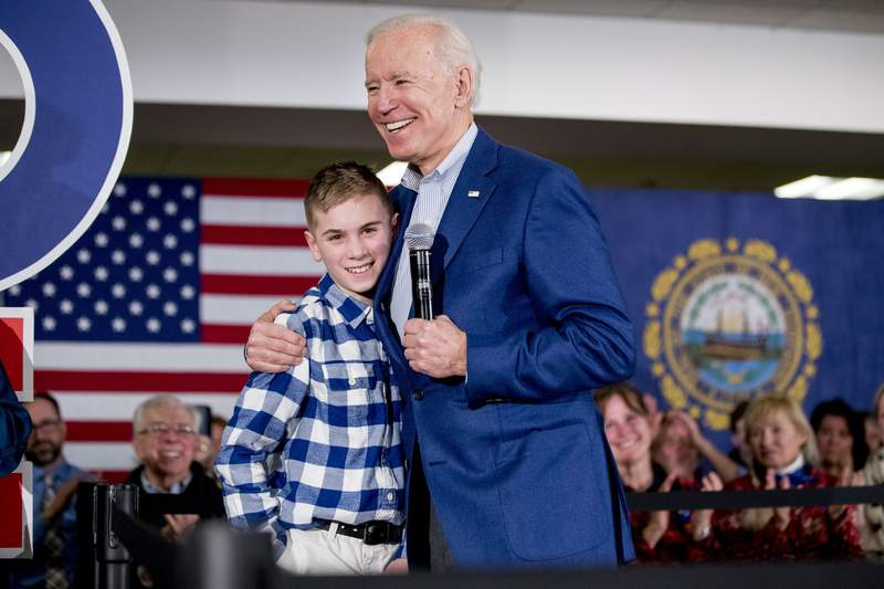FILE - Then Democratic presidential candidate former Vice President Joe Biden hugs Brayden Harrington at a campaign stop in Gilford, N.H. on Feb. 10, 2020. Harrington, who will be part of a primetime inaugural special, has a book coming out this summer. His picture story Brayden Speaks Up will be released Aug. 10. (AP Photo/Andrew Harnik, File)