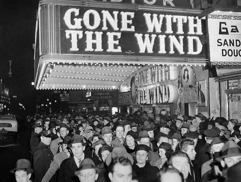 """FILE - In this Dec. 19, 1939 file photo, a crowd gathers outside the Astor Theater on Broadway during the premiere of """"Gone With the Wind"""" in New York. HBO Max has temporarily removed Gone With the Wind from its streaming library in order to add historical context to the 1939 film long criticized for romanticizing slavery and the Civil War-era South. (AP Photo)"""